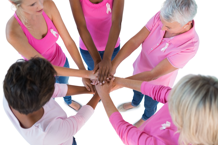 Group wearing pink and ribbons for breast cancer with hands together on white background