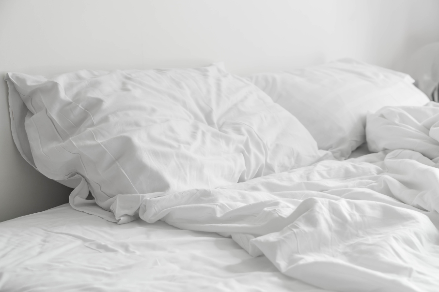 rumpled bed with white messy pillow decoration in bedroom