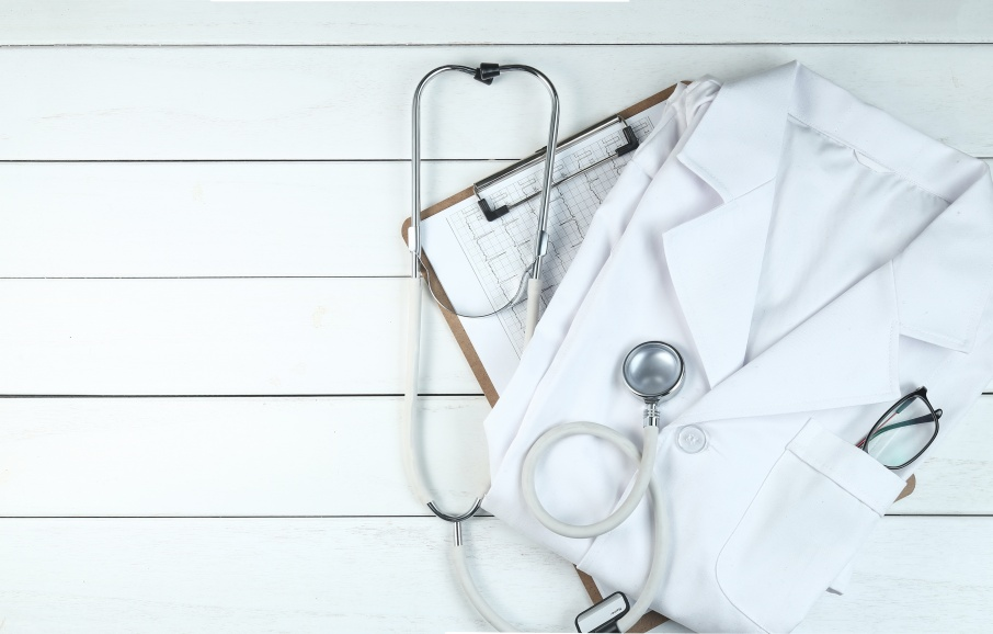 stethoscope,clipboard and doctor's uniform on white neat wooden desk
