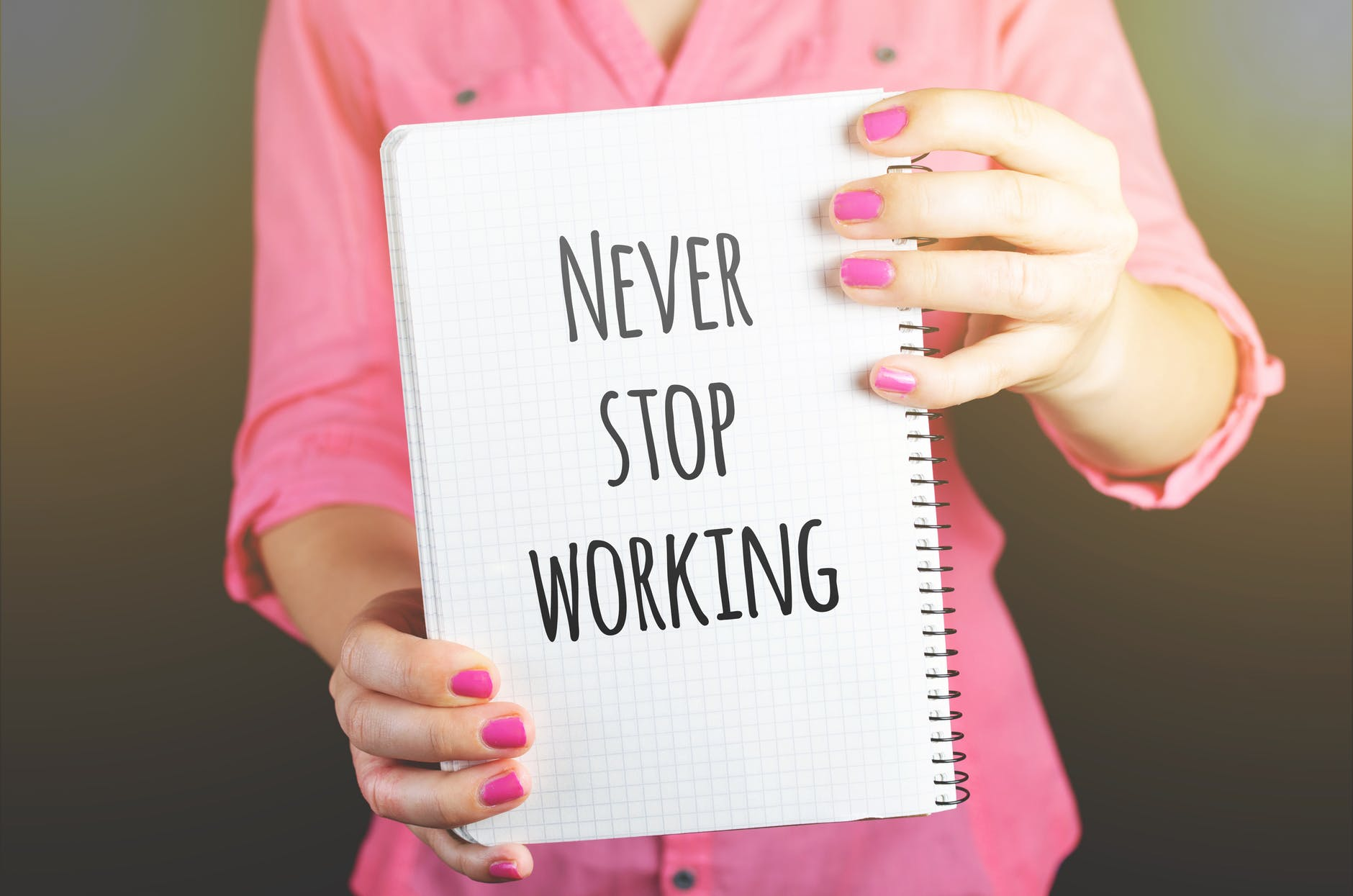 woman holding never stop working print notebook